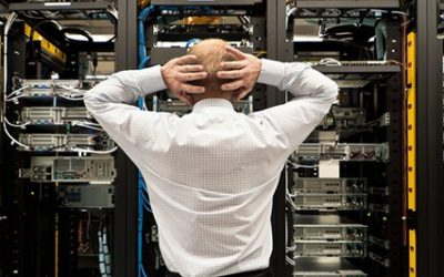 Man looking astonished in a network data center. Should have gotten disaster recovery.
